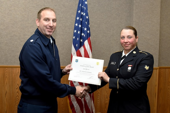 U.S. Air Force Lt. Col. Jason Kulchar, 315th Training Squadron director of operations, presents the 312th Training Squadron Student of the Month award for January 2017 to U.S. Army Spc. Amanda Miskiel, 312th TRS student, in the Brandenburg Hall on Goodfellow Air Force Base, Texas, Feb. 3, 2017. (U.S. Air Force photo by Staff Sgt. Joshua Edwards/Released)