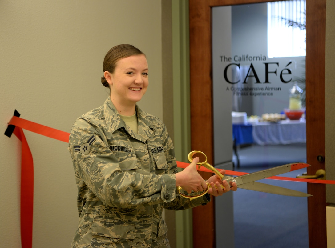 Airman First Class Aubrey, 9th Intelligence Squadron quality assurance specialist cuts the ribbon at the opening of the California CAFé, at the Beale Community Activity Center, Feb. 3, 2017, at Beale Air Force Base, California. CAFé is acronym for Comprehensive Airmen Fitness Experience. The CAFé lounge offers free coffee, Wi-Fi, and a full surround sound projection screen. (U.S. Air Force photo/ Staff Sgt. Bobby Cummings)