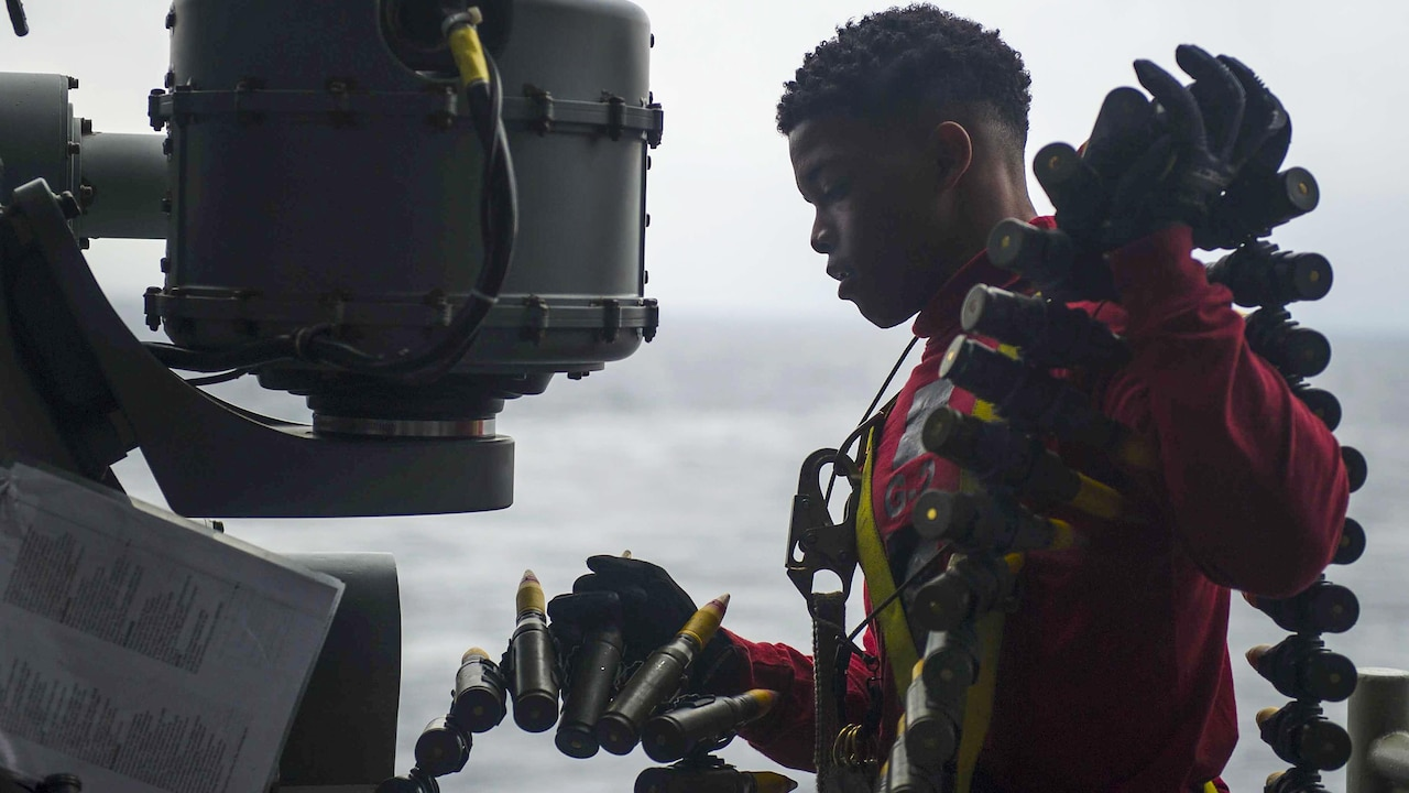 Navy Seaman Christian Wingate loads ammo into the Mark 38 machine gun for operational testing on the USS America in the Pacific Ocean, Feb. 2, 2017, as it prepares for deployment. Wingate is a gunner's mate. Navy photo by Petty Officer 3rd Class Arnesia McIntyre