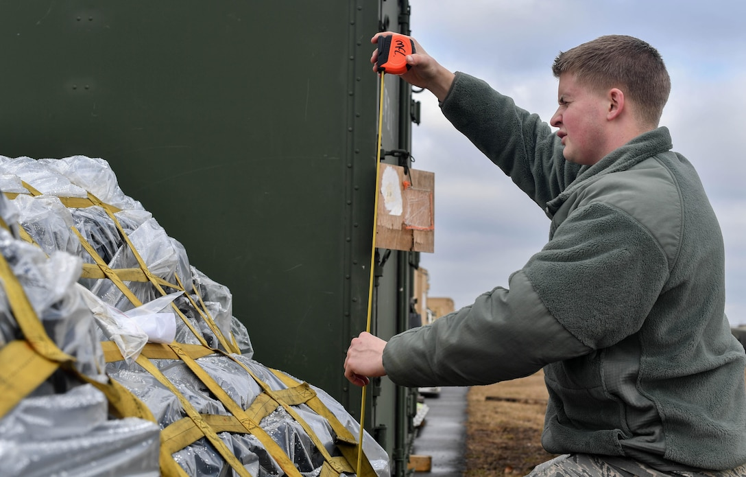 Airman Bryan McLaughlin, 86th Logistics Readiness deployment function air transportation specialist, measures the height of a pallet during the 435th Contingency Response Group's Exercise Austere Forge at Ramstein Air Base, Germany, Jan. 31, 2017. The 435 CRG worked hand-in-hand with the 86 Logistics Readiness Squadron and the 86th Vehicle Readiness Squadron during the exercise. Airmen in the 435 CRG participated in the exercise to practice their capability to deploy within 72 hours. (U.S. Air Force photo by Senior Airman Tryphena Mayhugh)