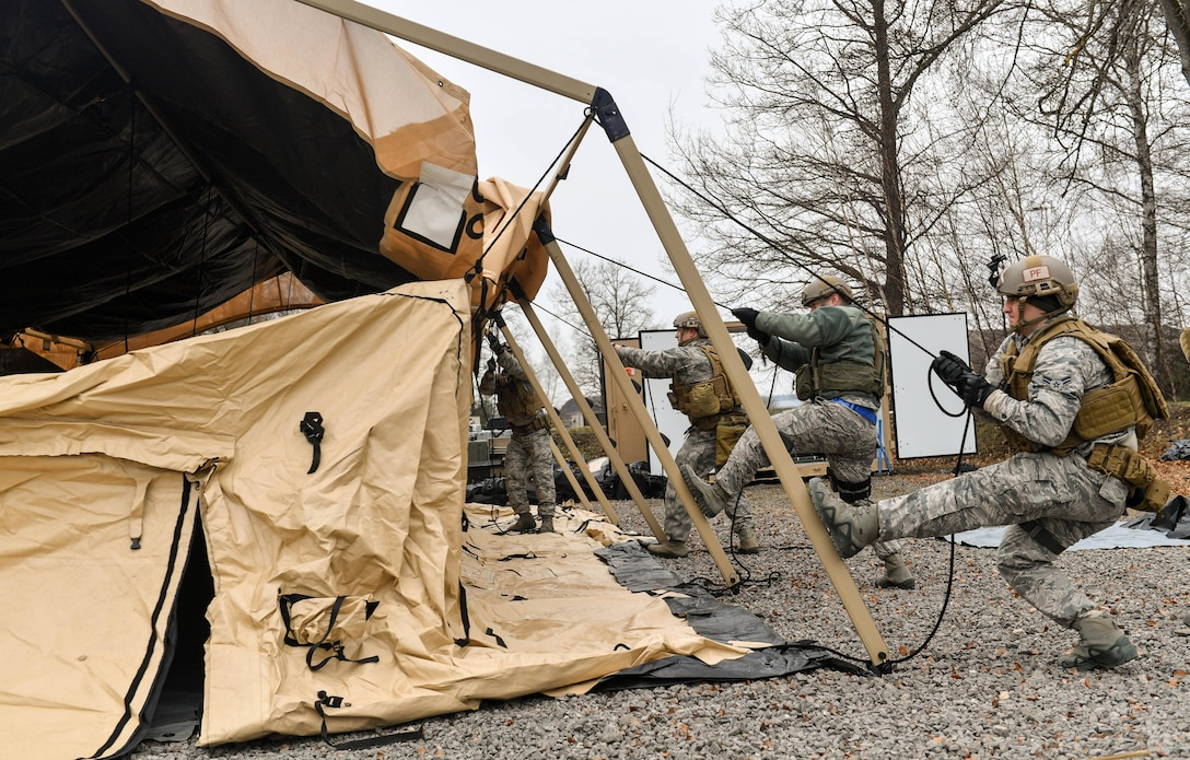 Airmen assigned to the 435th Contingency Response Group work together to build a tent during Exercise Austere Forge on Ramstein Air Base, Germany, Feb. 1, 2017. During the exercise, the Airmen planned what equipment would be used and who would be going, readied the equipment and personnel, processed through the 86th Logistic Readiness Squadron's installation deployment readiness cell, and set up tents and equipment in a simulated deployed location. The 435 CRG participated in the exercise to practice their capability to deploy within 72 hours. (U.S. Air Force photo by Senior Airman Tryphena Mayhugh)