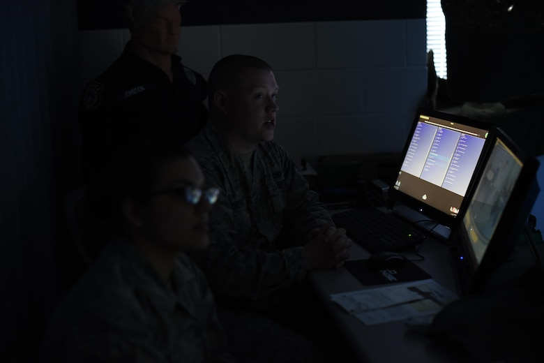 Staff Sgt. Tyler Cossentine, 22nd Security Forces Squadron NCO-in-charge of confinement, back and Staff Sgt. Kourtney Ruff, 22nd SFS NCOIC of training, evaluate the performance of other Defenders after using the Milo Range Training System, Feb. 1, 2017, at McConnell Air Force Base, Kan. Flight trainers will evaluate the users on their decisions to instill good habits and teach the reasoning behind the tactics. (U.S. Air Force photo/Senior Airman Christopher Thornbury)
