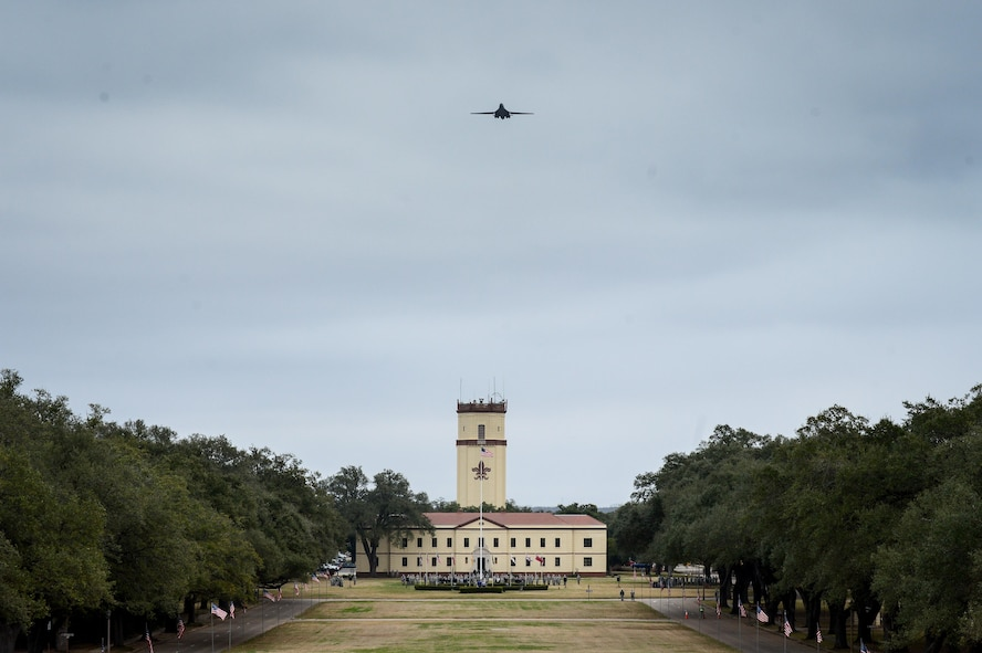"""A B-1B Lancer soars over the 2nd Bomb Wing headquarters building at Barksdale Air Force Base, La., in commemoration of the 8th Air Force's 75th anniversary Feb. 2, 2017. The modern day 8th Air Force traces its lineage to VIII Bomber Command, which came to life Feb. 1, 1942. Former and present bomber Airmen from across the country celebrated the anniversary by partaking in various event to honor the past, present and future Airmen of the """"Mighty Eighth."""" (U.S. Air Force photo by Senior Airman Mozer O. Da Cunha)"""