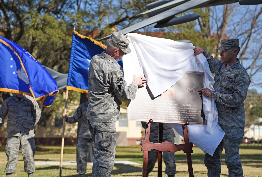 """Chief Master Sgt. Alan Boling, 8th Air Force command chief, and Maj. Gen. Thomas Bussiere, 8th AF commander, unveil a plaque during a building dedication ceremony at Barksdale Air Force Base, La., Feb. 2, 2017. The 8th AF headquarters building was dedicated to General James H. """"Jimmy"""" Doolittle during a series of 8th AF 75th diamond anniversary events. On Feb. 1, the Eighth celebrated its 75th anniversary, and former and current """"Mighty Eighth"""" Airmen from across the country came to Barksdale AFB to take part in the celebration. (U.S. Air Force photo by Senior Airman Erin Trower)"""