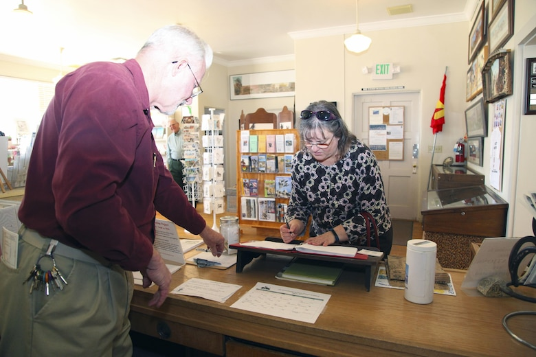 Vicki Mullen, wife of Brig. Gen. William F. Mullen III, Combat Center Commanding General, signs the guest book at the Old Schoolhouse Museum in Twentynine Palms, Calif., Jan. 31, 2017. With her is Twentynine Palms Historical Society President Les Snodgrass. The Mullens toured the facility with Sgt. Maj. Michael J. Hendges, Combat Center Sergeant Major; Cpl. Ben Mills, driver; Jim Ricker, Combat Center Assistant Chief of Staff for Government and External Affairs; and Kristina Becker, Combat Center External Affairs Director. (Official Marine Corps photo by Kelly O'Sullivan/Released)