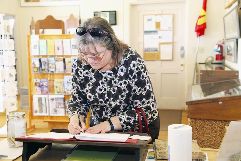 Vicki Mullen, wife of Brig. Gen. William F. Mullen III, Combat Center Commanding General, signs the guest book at the Old Schoolhouse Museum in Twentynine Palms, Calif., Jan. 31, 2017. The Mullens toured the facility with Sgt. Maj. Michael J. Hendges, Combat Center Sergeant Major; Cpl. Ben Mills, driver; Jim Ricker, Combat Center Assistant Chief of Staff for Government and External Affairs; and Kristina Becker, Combat Center External Affairs Director. (Official Marine Corps photo by Kelly O'Sullivan/Released)