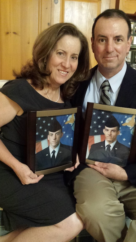 Roxann Burns and retired Chief Master Sgt. Bryan Burns, 60th Operations Support Squadron, pose for a photo in their home Feb. 7, 2017, while holding a photograph of their two children, Matthew and Joshua Burns. Matthew joined the Air Force and is currently a staff sergeant assigned to the 79th Air Refueling Squadron at Travis Air Force Base, Calif. Joshua also joined the Air Force and served nearly nine years as a KC-10 Extender boom operator. (Courtesy Photo)