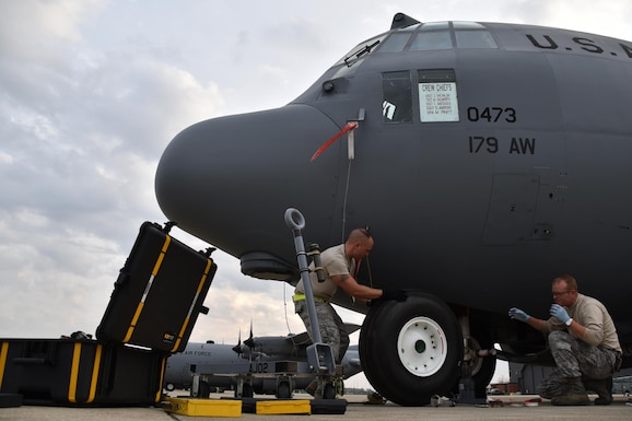 Master Sgt. Zac Michalski and Tech. Sgt. Mark Dulworth change a tire of a C-130H Hercules on the flightline Nov. 2, 2016, at the 179th Airlift Wing, Mansfield, Ohio. The Ohio Air National Guard unit is always on mission to respond with highly qualified citizen airmen to execute Federal, State and community missions. (U.S. Air National Guard photo by Airman Megan Shepherd\Released)
