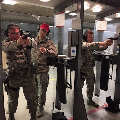 Staff Sgt. Matthew Lockard, left, and Staff Sgt. Bryan Clark, right, take instruction from Senior Airman Bryan Effingham Feb. 3 as members of the 178th Security Forces Squadron, Ohio Air National Guard, based in Springfield, sharpen their combat shooting skills at the Combat Arms facility at Wright-Patterson Air Force Base. The facility will host an Excellence in Competition for pistol and rifle categories in April. (Skywrighter photo/Amy Rollins)