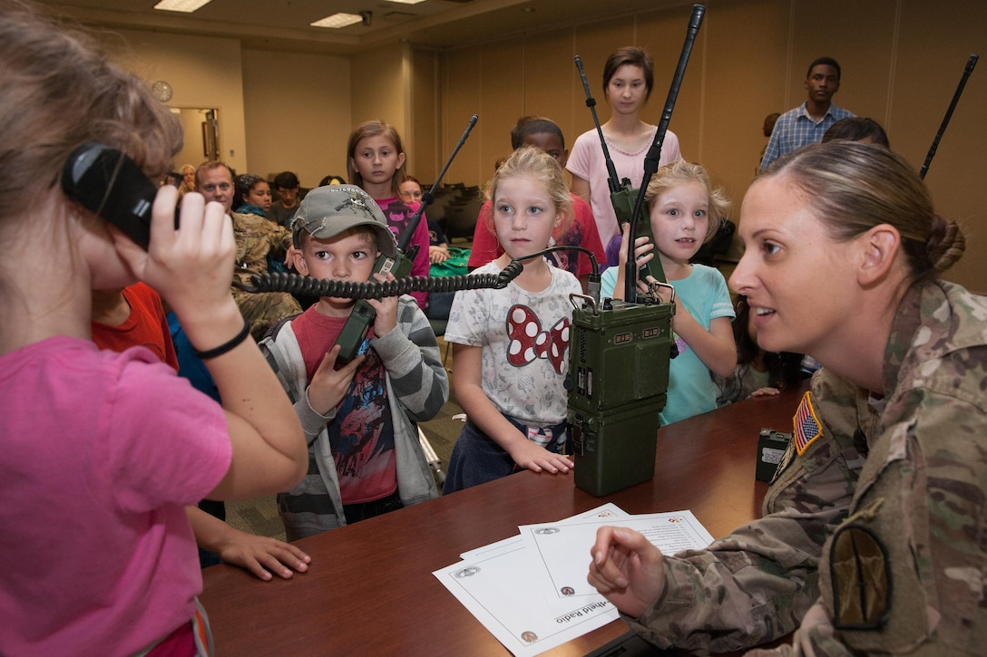A member of U.S. Special Operations Command South listens as students use military radios