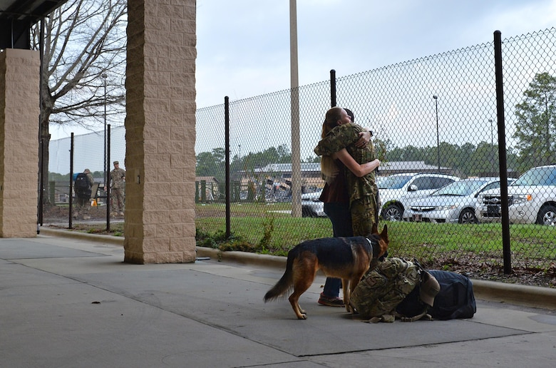 Staff Sgt. Jeremy Wolski, a loadmaster with the 15th Special Operations Squadron, is greeted by his wife and dog during an Operation Homecoming at Hurlburt Field, Fla., Feb. 7, 2017. Close to 190 Air Commandos were greeted by friends and family upon returning home from deployed locations. (U.S. Air Force photo by Senior Airman Andrea Posey)