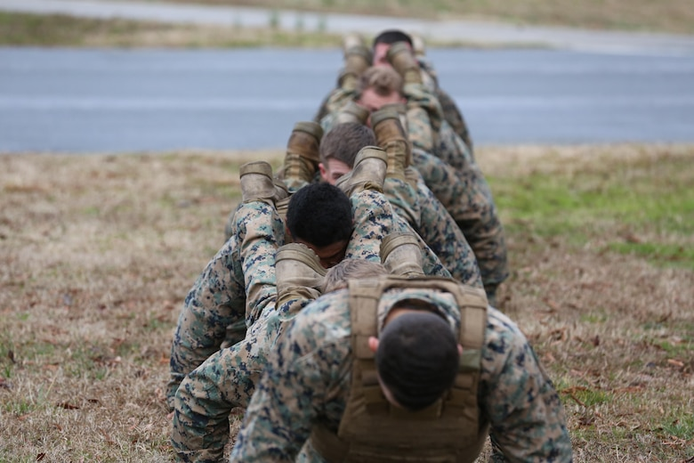 Marines execute squad push-ups during the culminating event of a Martial Arts Instructor course aboard Marine Corps Air Station Cherry Point, N.C., Feb. 3, 2017. The Marines completed 15 rigorous training days to become martial arts instructors. The course tested the Marines mentally and physically as they learned the ethos of the Marine Corps Martial Arts Program. More than 20 Marines from various units aboard the air station graduated the course. (U.S. Marine Corps photo by Lance Cpl. Cody Lemons/Released)