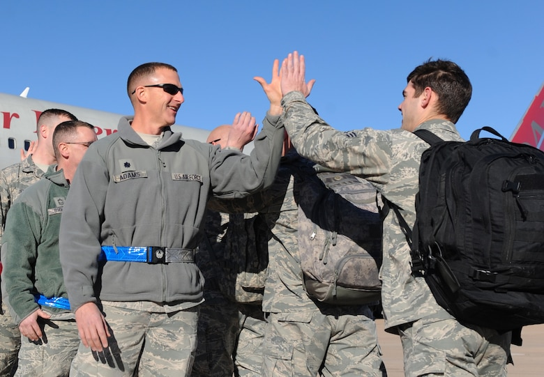 U.S. Air Force Lt. Col. John Adams, 7th Aircraft Maintenance Squadron commander, (left) high-fives  deploying Airmen at Dyess Air Force Base, Texas, Jan. 31, 2017. Team Dyess commanders, supervisors and first sergeants wished the more than 300 personnel a safe deployment. (U.S. Air Force photo by Airman 1st Class Emily Copeland)