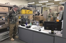 Harrold Stafford, left, 1st Infantry Division Sustainment Brigade safety officer, shows Sgt. Dustin Stambaugh, far right, test, measurement and diagnostic equipment sergeant, adjustments to meet the safety requirements for the TMDE shop Dec. 7. This was an opportunity for TMDE to identify and control hazards prior to the shop conducting calibration for all 1st Inf. Div. units.