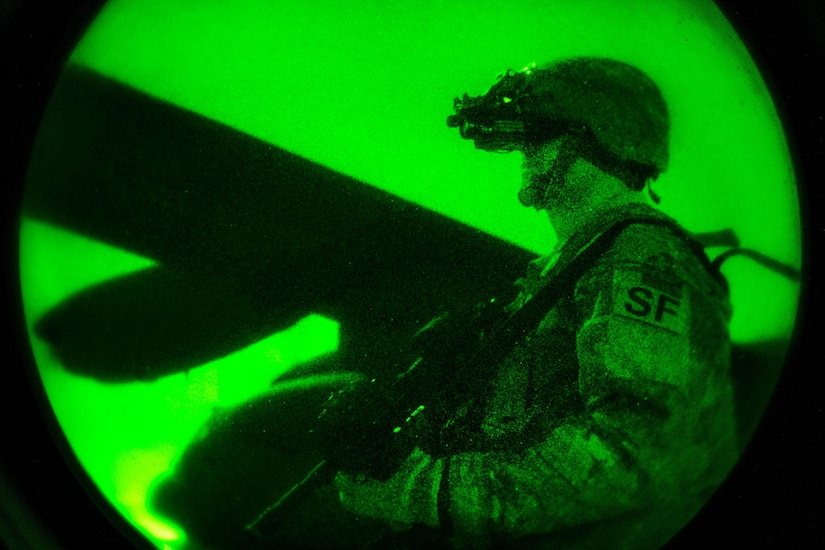 As seen through a night vision device, Air Force Tech Sgt. Brady Mueller guards the perimeter of a C-130H Hercules aircraft in Iraq, Dec. 15, 2016. Muller is a security team member assigned to the 386th Expeditionary Security Forces Squadron. Air Force photo by Senior Airman Jordan Castelan