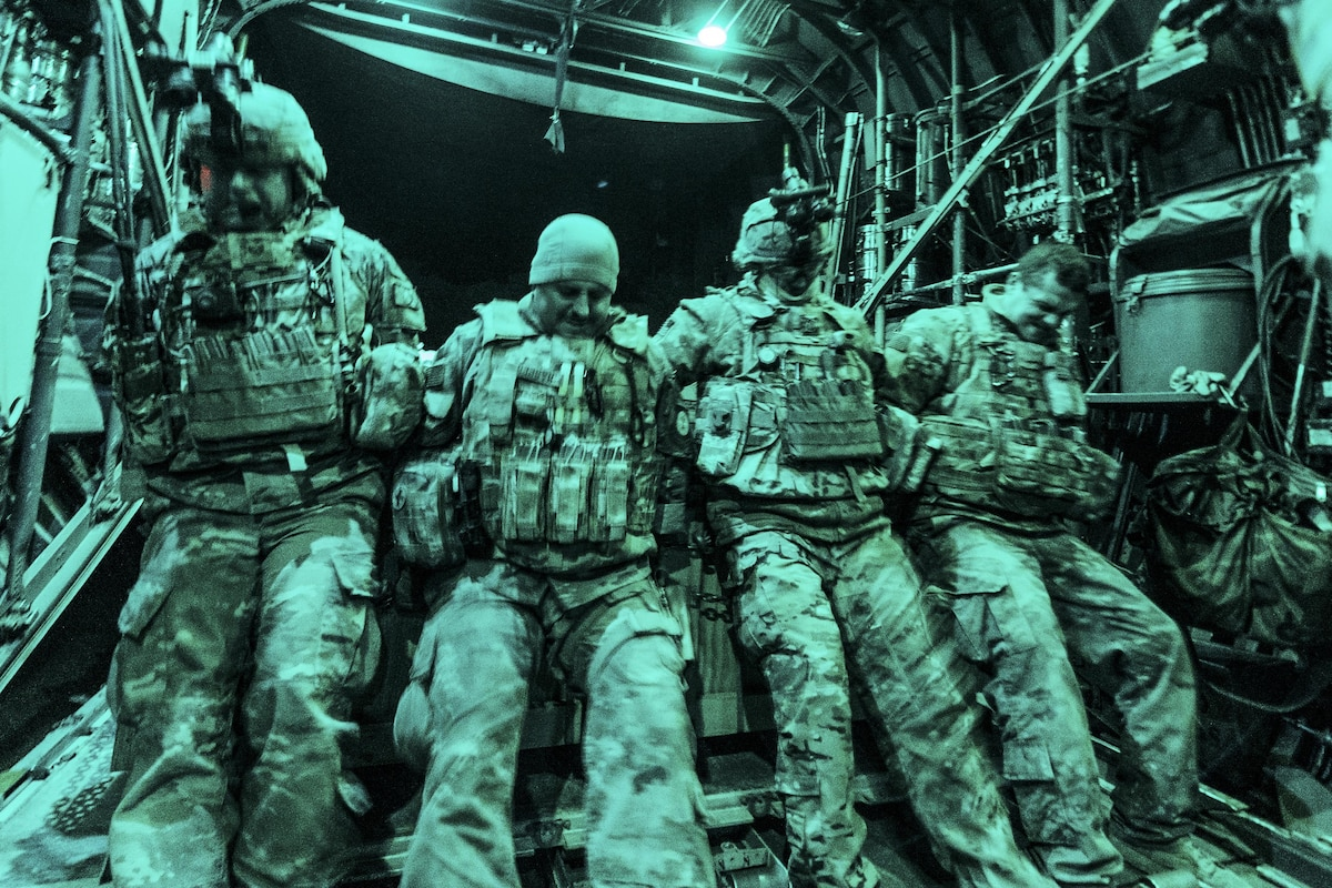 Airmen secure a load of cargo in an aircraft at night.