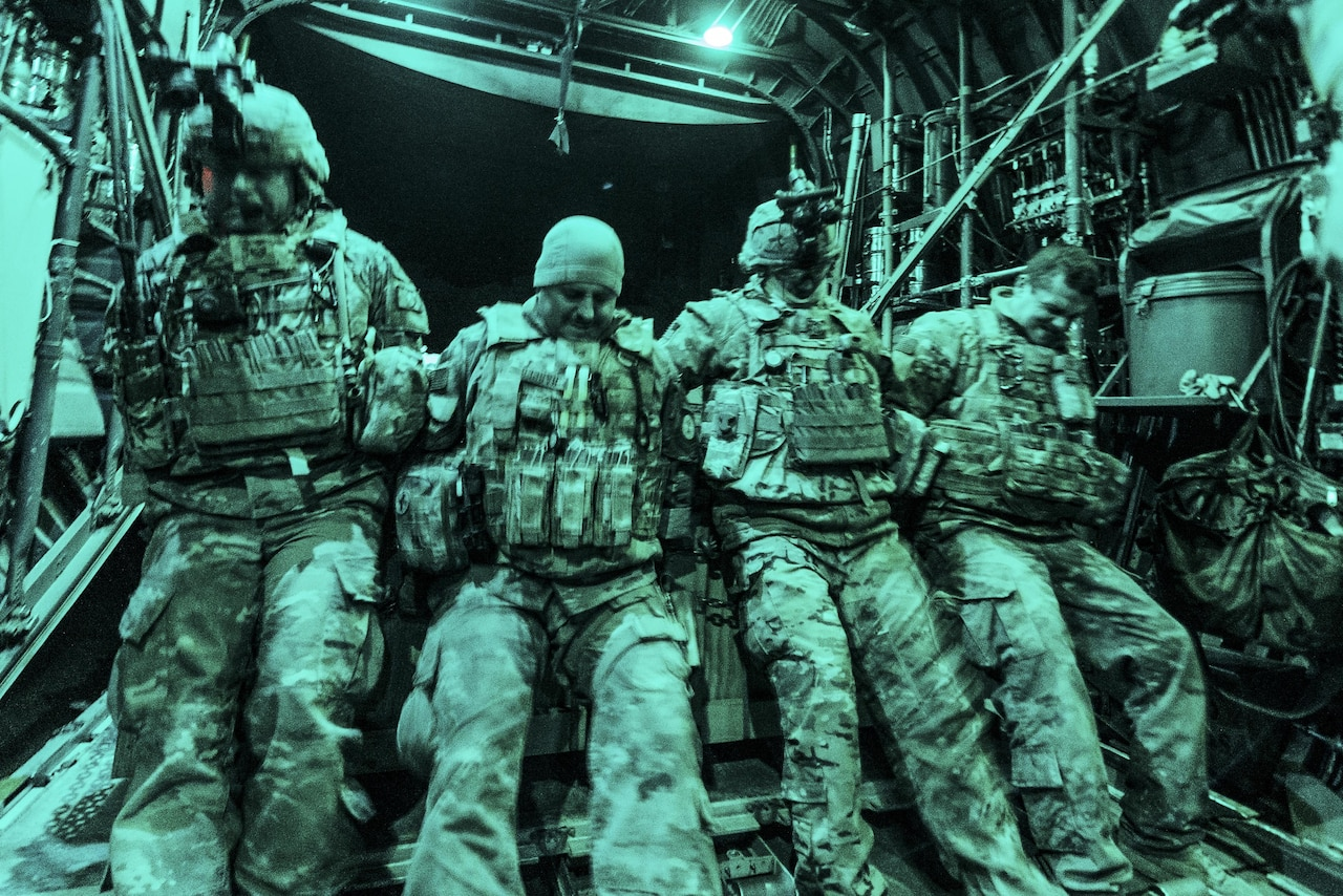 Four airmen, illuminated by green light, lean into a load of cargo to push it onto an aircraft.
