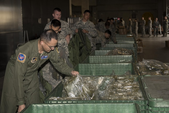 U.S. Air Force Airmen pick up Mission-Oriented Protective Posture gear during an exercise Feb. 7, 2017, at Kadena Air Base, Japan. In the event of an actual chemical attack, Airmen must be able to quickly and efficiently acquire all essential MOPP gear and equipment in order to complete mission objectives. (U.S. Air Force photo by Airman 1st Class Corey M. Pettis/Released)