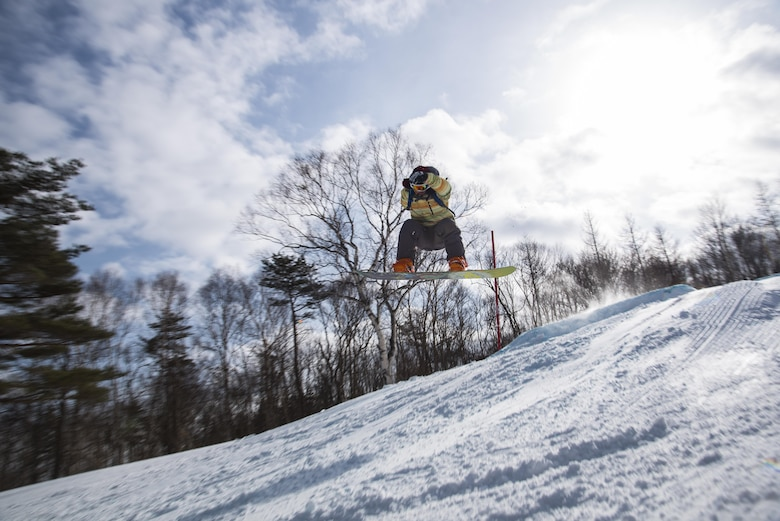 U.S. Air Force Airman 1st Class Alexander Crutchfield, a 35th Maintenance Squadron structures technician, makes a jump at a ski resort in Hachimantai, Japan, Jan. 29, 2017. Airmen from many shops had the opportunity to ski or snowboard to practice the four Air Force resiliency pillars including: physical, spiritual, mental and social domains. (U.S. Air Force photo by Airman 1st Class Sadie Colbert)