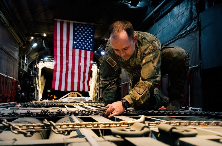 Senior Airman Creg Dubois, a 737th Expeditionary Airlift Squadron loadmaster, secures cargo before take-off inside a C-130H Hercules at an undisclosed location in Southwest Asia, Feb. 3, 2017. Dubois is part of a team that delivered 30,000 pounds of cargo to aide in the fight against ISIL. (U.S. Air Force photo/Senior Airman Jordan Castelan)