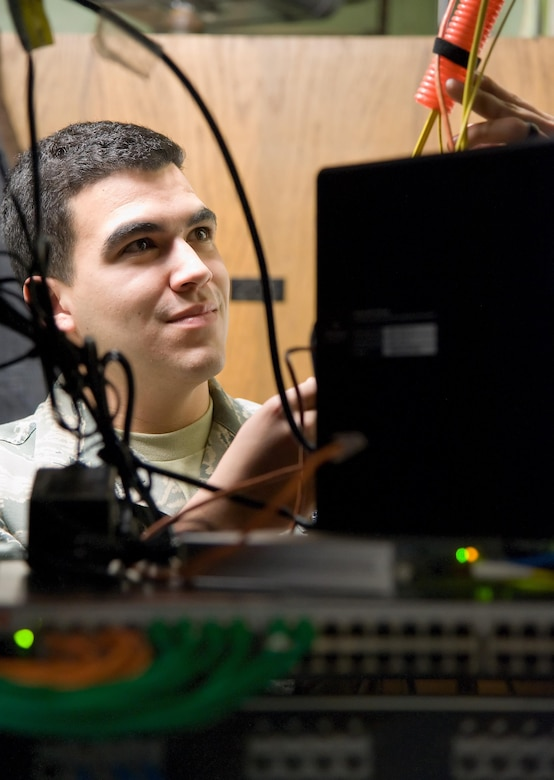 Airman 1st Class Jeffrey Bailey-Oqueli, 436th Communications Squadron cyber transport system technician, checks cables routed to newly installed communication switches Feb. 3, 2017, on Dover Air Force Base, Del. Bailey-Oqueli and contractors upgraded network hardware in building 201 as part of Dover's network modernization project. (U.S. Air Force photo by Roland Balik)