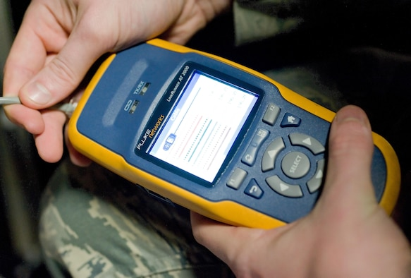 Airman 1st Class Jeffrey Bailey-Oqueli, 436th Communications Squadron cyber transport system technician, checks a network cable connection in the wing conference room Feb. 3, 2017, on Dover Air Force Base, Del. Bailey-Oqueli use a Fluke Networks LineRunner 2000 to check connectivity as well as the total length of the cable coming from the second floor communications closet. (U.S. Air Force photo by Roland Balik)