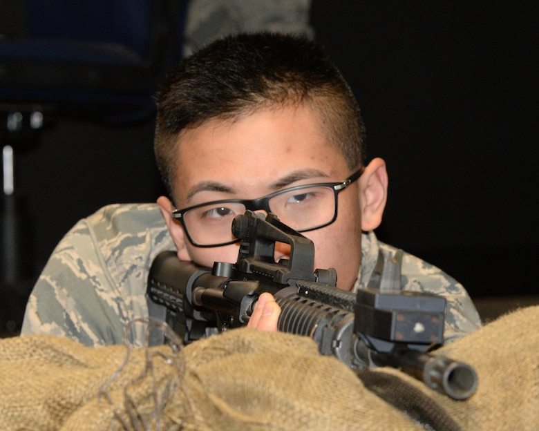 U.S. Air Force Airman 1st Class Hoang Nguyen, New Hampshire Air National Guard Student flight trainee, fires an M-4 rifle in the Firearms Training Simulator at the New Hampshire Army National Guard's Training Site, Center Strafford, N.H., Feb. 4, 2017.  The weapons familiarization prepares Airmen for basic training. (U.S. Air National Guard photo by Staff Sgt. Curtis J. Lenz)