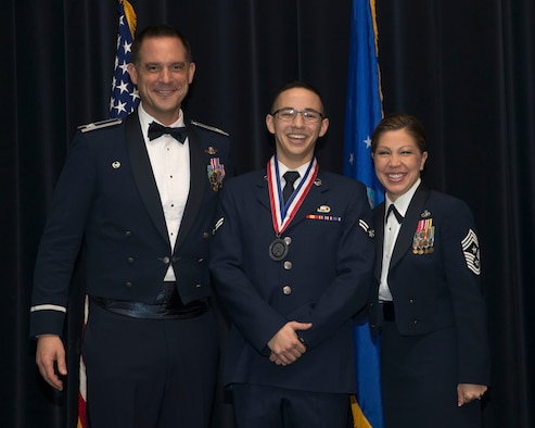 Col. Ethan C. Griffin, 436th Airlift Wing commander,  and Chief Master Sgt. Sarah Sparks, 436th AW command chief,  poses with Airman 1st Class Justin Schindlbeck, 436th Comptroller Squadron financial services technician, at the 2016 436th AW Annual Awards Ceremony Feb. 3, 2017, at the Rollins Center inside of Dover Downs, Dover, Del. Before the start of the event, nominees in each of the 14 categories were called to the stage to be recognized for their hard work. Individual categories nominees received medallions. (U.S. Air Force photo by Staff Sgt. Jared Duhon)