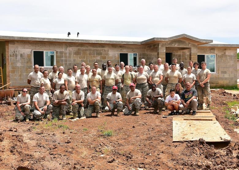 Members of the 143d Civil Engineering Squadron and Public Affairs pose with members of the Guam Innovative Readiness Training Support Team and members of the family chosen by Habitat for Humanity, Guam to receive one of the houses being built. The 143 CES and PA teams are in Guam supporting Habitat for Humanity, Guam through the Innovative Readiness Training program building two houses for deserving local families. Air National Guard photo by Master Sgt Janeen Miller
