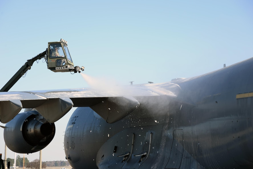 A member of the 43rd Air Mobility Squadron de-ices at C-17 Globemaster III on Pope Army Airfield's Green Ramp prior to loading cargo Jan. 8, 2017. The 43rd Air Mobility Operations Group handles all aircraft maintenance and aerial port operations for transient aircraft moving through Pope AAF. It is the only air mobiity operations group in the continental U.S. (U.S. Air Force photo by Master Sgt. Thomas J. Doscher)