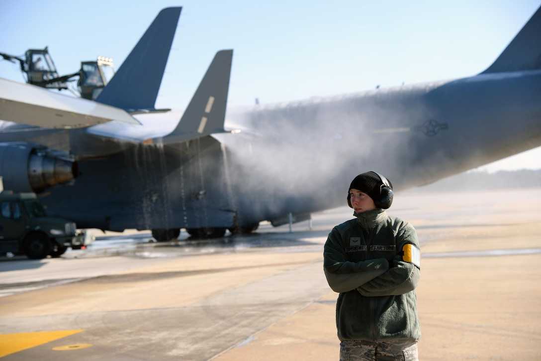 Airman 1st Class Kursten Davenport, 43rd Air Mobility Squadron ramp operator, stands by to load a C-17 Globemaster III on Pope Army Airfield's Green Ramp Jan. 8, 2017, while other 43rd AMS members de-ice a second C-17 behind her. An ice storm shut down most of North Carolina the previous day, delaying a Deployment Readiness Exercise. (U.S. Air Force photo by Master Sgt. Thomas J. Doscher/Released)
