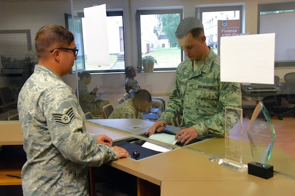 Air Force Staff Sgt. Kelly Querry, left, with the Ohio Air National Guard's 178th Wing Financial Management section, processes a payment voucher for a customer at Ramstein Air Base, Germany, in July 2016. Maintaining strong financial health is important for National Guard members to remain mission ready, said Guard officials. For those who may need financial planning assistance, a variety of resources are available at many military installations.