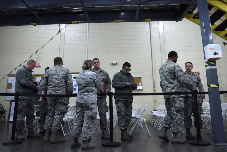U.S. Air Force Tech. Sgt. Alejandro Armendariz (center), 145th Maintenance Squadron, clips together his dog tags while waiting in line during a deployment processing line held at the held at the North Carolina Air National Guard Base, Charlotte Douglas International Airport, Feb. 5, 2017. Armendariz is a crew chief and is deploying for the first time to maintain C-130 Hercules aircraft in support of Operation Freedom Sentinel to provide tactical airlift in the region.