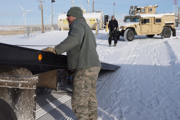 Senior Airmen Leonard Montoya, left, and Ian Lauzon, both 341st Logistics Readiness Squadron vehicle operators, prepare to move a Humvee onto the back of a tow truck at a missile alert facility which will later be transferred to Malmstrom Air Force Base, Mont., for maintenance Feb. 7,2017.  (U.S. Air Force photo/Jason Heavner)