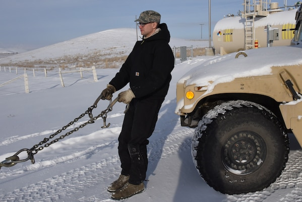 Senior Airman Ian Lauzon, 341st Logistics Readiness Squadron vehicle operator, prepares to connect towing cables to a Humvee at a missile alert facility Feb. 7, 2017.  The Humvee will be towed to Malmstrom Air Force Base, Mont., for maintenance.  (U.S. Air Force photo/Jason Heavner)