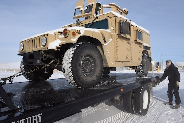 Senior Airman Ian Lauzon, 341st Logistics Readiness Squadron vehicle operator, adjusts the ramp of a tow truck in preparation for transferring a Humvee to Malmstrom Air Force Base, Mont., for maintenance Feb. 7, 2017.  In addition to vehicles needing repair, the 341 LRS vehicle operators maintain a fleet of more than 800 government vehicles that travel both on base and in the nearly 13,800 square mile missile field located in central Montana.  (U.S. Air Force photo/Jason Heavner)