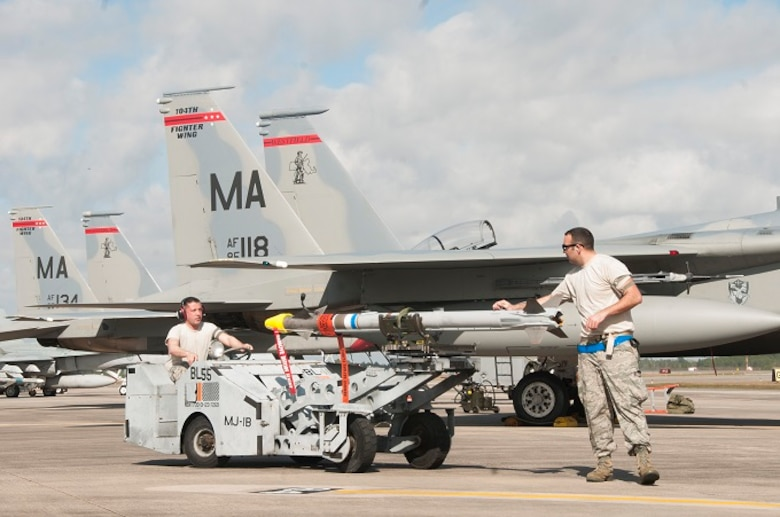 Staff Sgt. Timothy Mannion, the Three Man on the load crew, drives the jammer while Tech. Sgt. Lucas Hagopian, Weapons Load Crew Chief, oversees the load crew arming the 104th Fighter Wing's F-15 Eagle operations at the U.S. Air Force's Weapons System Evaluation Program at Tyndall, Air Force Base. The purpose of WSEP is to gauge operational effectiveness, to verify weapons system performance, determine reliability, and evaluate capability. (U.S. Air National Guard Photo by Senior Master Sgt. Julie Avey)