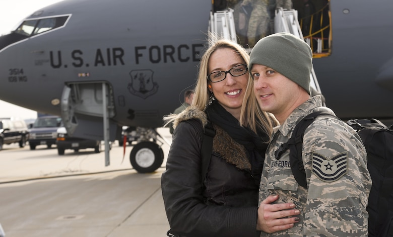 Technical Sergeant Bjorn Fecher, 108th Aerospace Ground Equipment, reunites with his girl friend Jessica Jaquis, at Joint Base McGuire-Dix-Lakehurst, N.J., Dec. 21, 2016. This is Tech. Sgt. Fecher's 7th deployment in 15 years. (U.S. Air National Guard photo by Staff Sgt. Ross A. Whitley/Released)