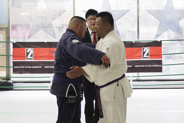 U.S. Marine Corps Master Sgt. Marcos Martinez, expeditionary fire rescue staff noncommissioned officer in charge with Marine Wing Support Squadron (MWSS) 171, left, leans in to hug his opponent after their match during the Duamau Tournament, a jiu jitsu competition at the TK Training Center in Hiroshima, Japan, Feb. 5, 2017. Jiu jitsu is a sport that teaches competitors to respect their opponents and build on the differences. Martinez trains among other Marines at the IronWorks North gym on Marine Corps Air Station Iwakuni. (U.S. Marine Corps photo by Lance Cpl. Joseph Abrego)