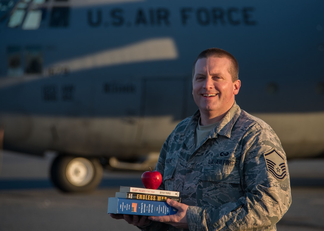 Master Sgt. Jason Paseur, the 386th Air Expeditionary Wing historian, poses for a photo in front of a C-130H Hercules at the flightline here Feb. 7, 2017. Paseur is a reservist deployed from Dobbins Air Reserve Base, Ga. and teaches history as a civilian. (U.S. Air Force photo/Senior Airman Andrew Park)