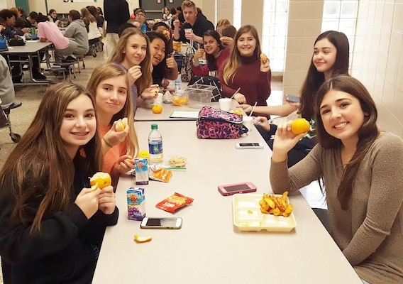 Students at Discovery Middle School in Madison, Alabama hold up their Alabama-grown satsumas during lunch. DLA Troop Support's Subsistence supply chain provides satsumas to Alabama schools through Department of Defense Fresh program.