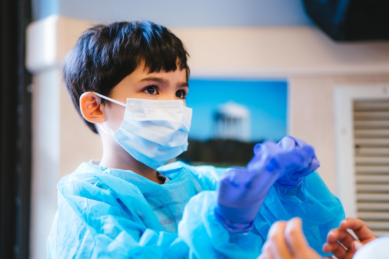 A child tries on a dental gown, mask and gloves at the Child Development Center at Joint Base Andrews, Md., Feb. 3, 2017. Members of the 779th Dental Squadron visited children to share information about the base's dental clinic as well as techniques to maintain good oral hygiene. (U.S. Air Force photo by Senior Airman Delano Scott)