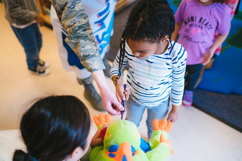 Members of the 779th Dental Squadron show a child how to brush teeth at the Child Development Center at Joint Base Andrews, Md., Feb. 3, 2017. Airmen from the 779th Dental Squadron, in support of Children's Dental Health Month, visited the base's CDC to speak with children about healthy eating, proper brushing, flossing and the importance of visiting a dentist regularly. (U.S. Air Force photo by Senior Airman Delano Scott)