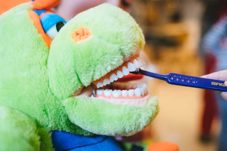 A child brushes a dinosaur puppet's teeth at the Child Development Center at Joint Base Andrews, Md., Feb. 3, 2017. As part of National Children's Dental Health Month, 779th Dental Squadron Airmen spoke with children about brushing, flossing and eating healthy snacks. (U.S. Air Force photo by Senior Airman Delano Scott)