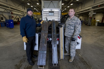 """Teddy Manning, left, 375th Logistics Readiness Squadron chief of personal property, shows different iterations of the Meyer's Bar during its development at Scott Air Force Base, Ill., Jan. 19, 2017. The """"Meyer's Bar 2.0"""" is a 5-foot reinforced steel bar that supports a lowboy trailer's hydraulic gooseneck hitch to prevent it from bending. Air Force photo by Senior Airman Joshua Eikren"""