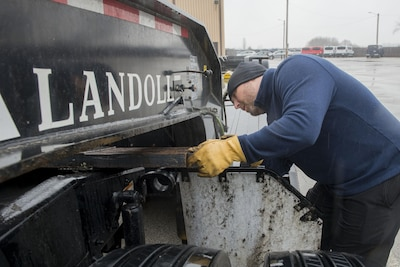 Teddy Manning, 375th Logistics Readiness Squadron chief of personal property, positions the Meyer's Bar onto the hitch of the lowboy at Scott Air Force Base, Ill., Jan. 19, 2017. Manning assisted in the bar's creation. Air Force photo by Senior Airman Joshua Eikren