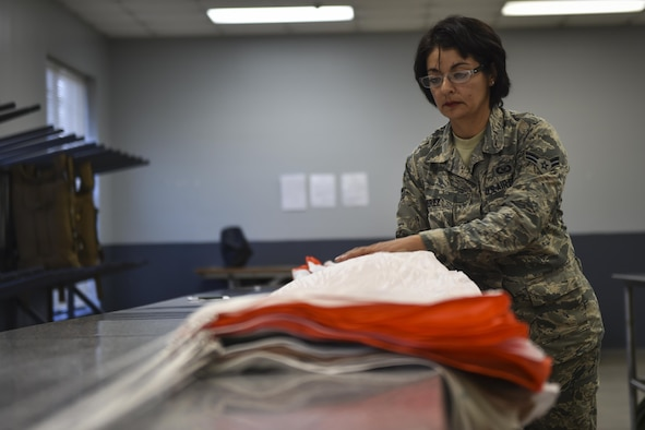Airman 1st Class Maria Perez, an aircrew flight equipment specialist with the 4th Special Operations Squadron, checks the lines of a low-profile parachute at Hurlburt Field, Fla., Jan. 25, 2017. The equipment specialists are responsible for maintaining flight equipment such as helmets, oxygen masks, harnesses and all life-saving equipment. (U.S. Air Force photo by Airman 1st Class Joseph Pick)