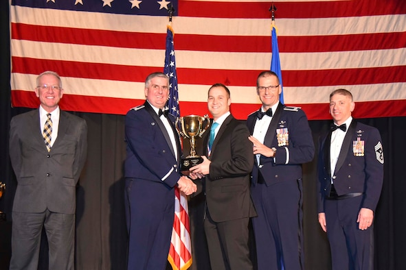 Ryan H. Lee, 22nd Security Forces Squadron, center, accepts the 2016 Civilian Category I of the Year award, Feb. 3, 2017, at McConnell Air Force Base, Kan. The annual awards ceremony recognized military and civilian members who excel in their areas of responsibilities, leadership qualities, community involvement, self-improvement and innovation from of January to December 2016. (U.S. Air Force photo/Senior Airman Christopher Thornbury)