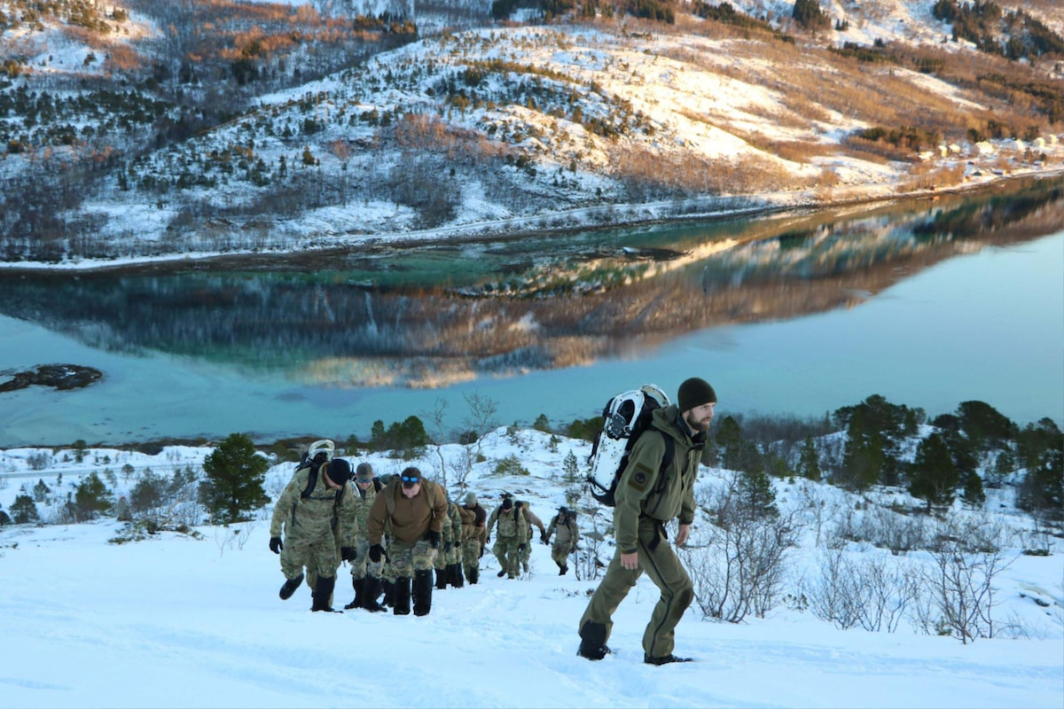 U.S. and Norwegian troops trek through snow uphill.