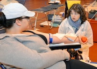 Alicia Murgolo, left, 48th Civil Engineer Squadron spouse, discusses the donation process with Pamela Hudson, phlebotomist technician from the Armed Services Blood Program-Europe, Landstuhl Regional Medical Center, Germany, as she gives blood Feb. 7, 2017, on RAF Mildenhall, England. More than 70 units of blood were donated by Team Mildenhall members, which will be used to support missions in European Command, Central Command and Africa Command, as well as in military treatment facilities.    (U.S. Air Force photo by Karen Abeyasekere)